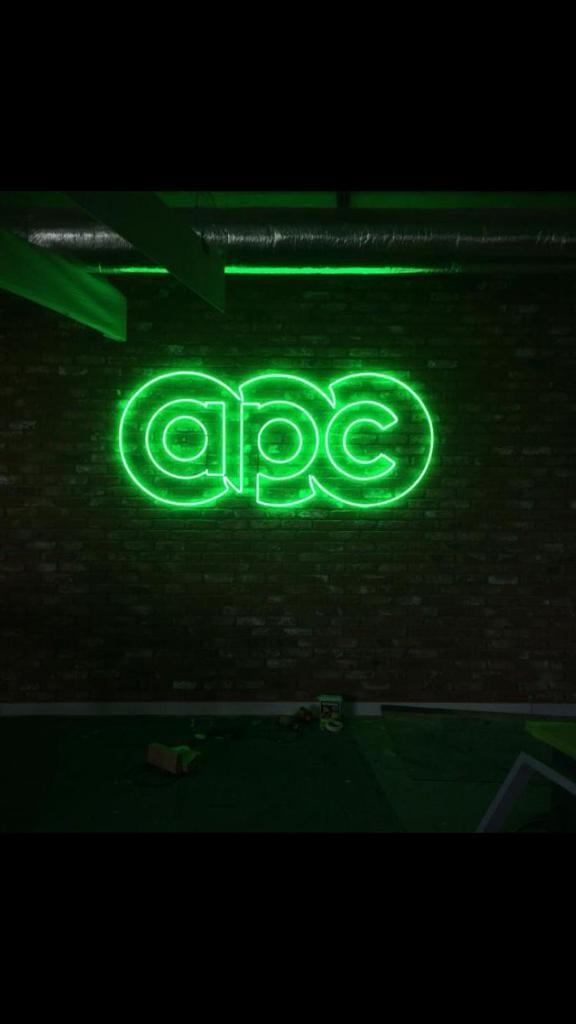 Neon APC Logo glowing on a brick wall