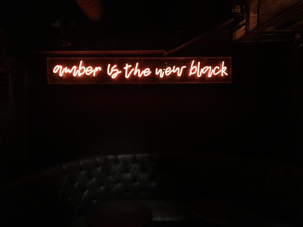 Neon Amber is the new black sign with a script style