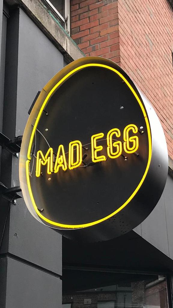 mad egg logo yellow illuminated sign shopfront