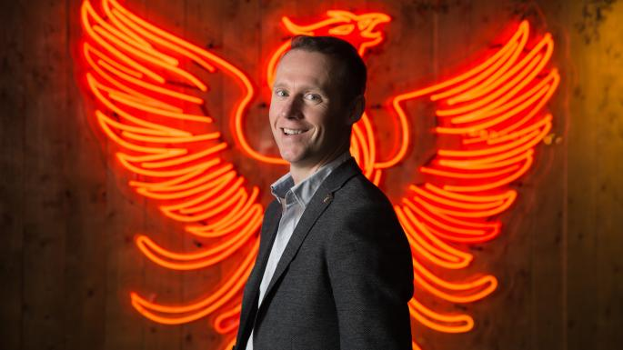 The owner of Teelings Whiskey standing in front of the Neon Phoenix Sign